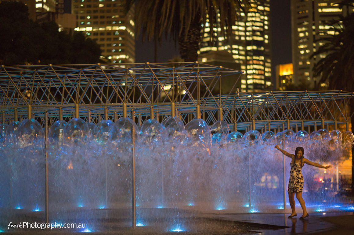 Girl dancing in fountain in the Melbourne CBD at night - enjoy Melbourne - the most liveable city in the world