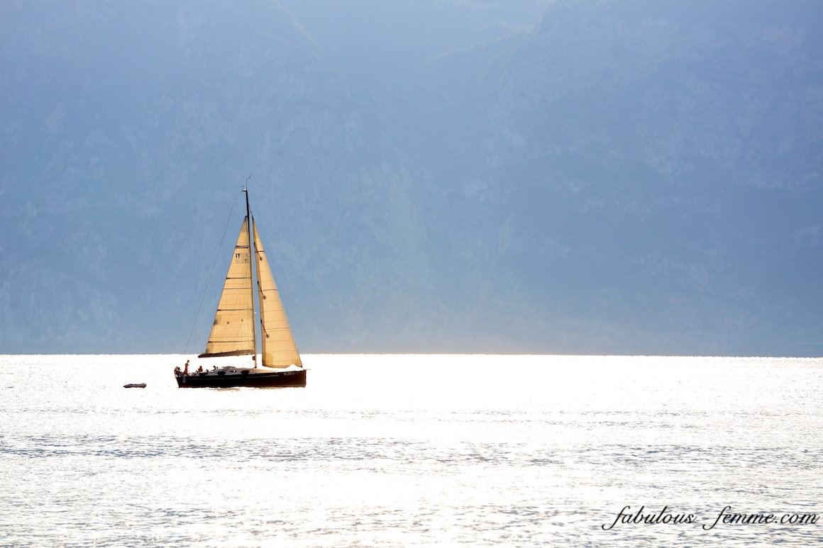 sailing boat on lake garda, italy - backlit