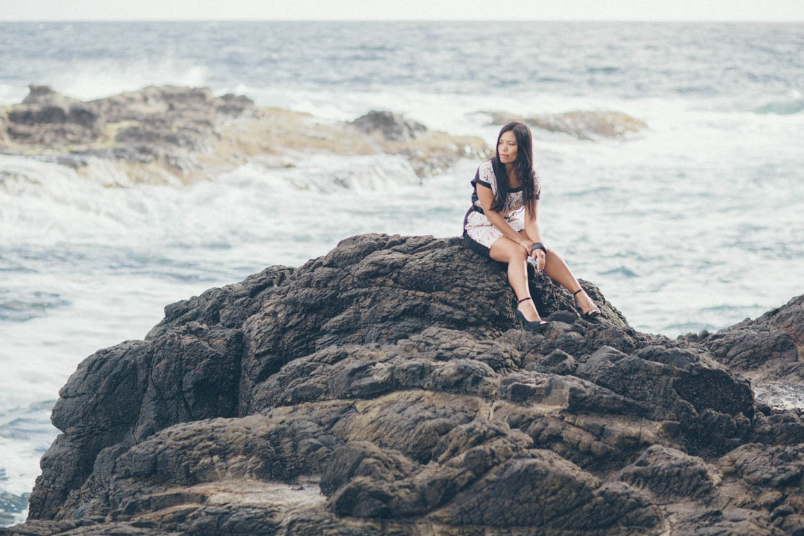 girl sitting on the rocks - waves in the background - ocean