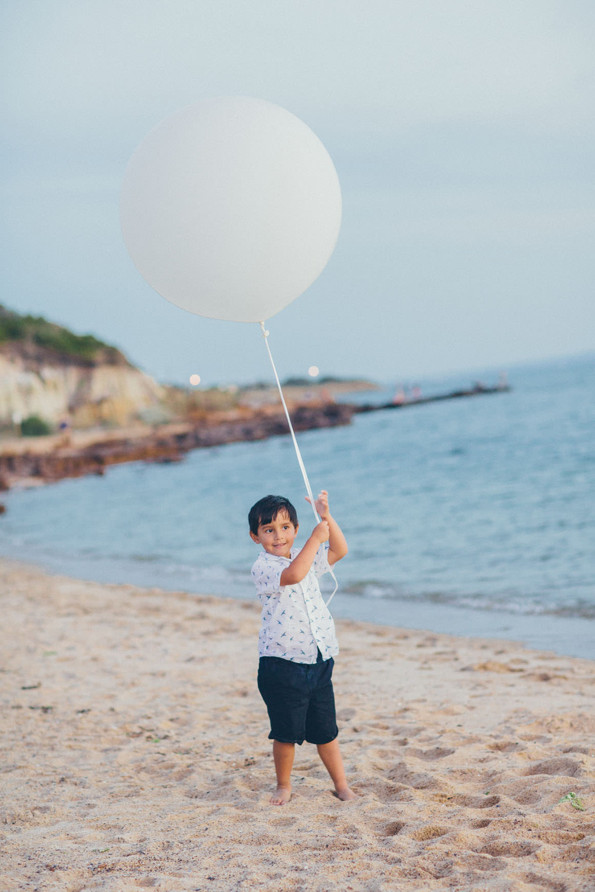 boy at the beach with balloon