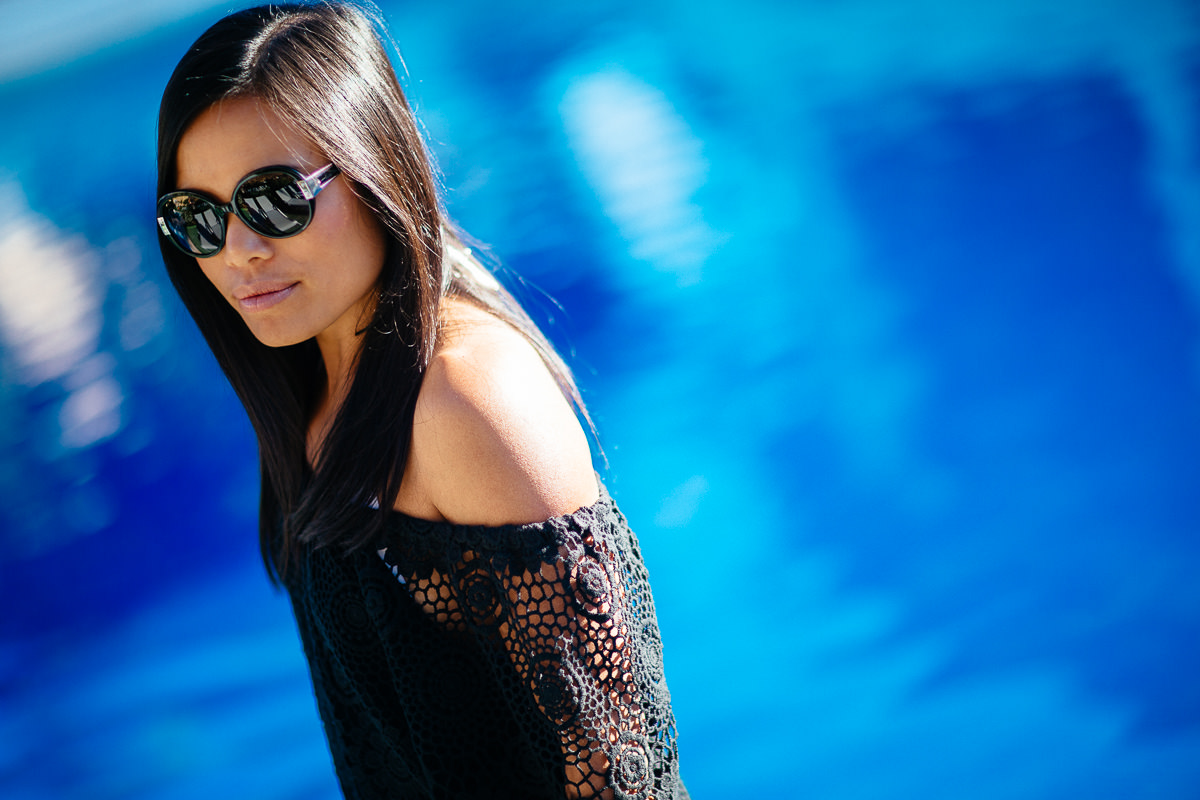 summer sun and sunglasses - blue pool and black outfit poolside in spain - luxury pure