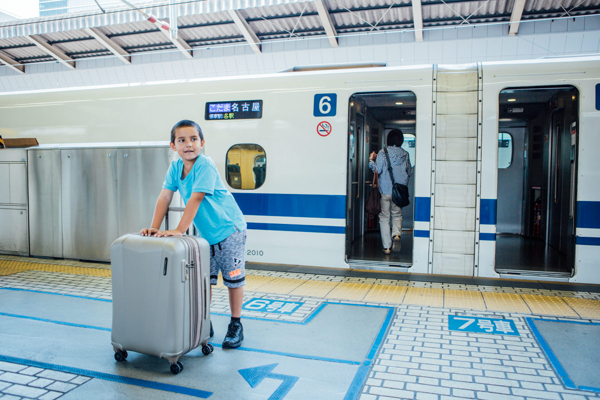 Little boy carries suitcase - travel in japan on the shinkansen high speed train
