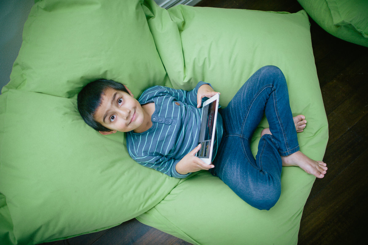 kid using portable internet - ipad - in bean bag - fun lifestyle photography - portable internet