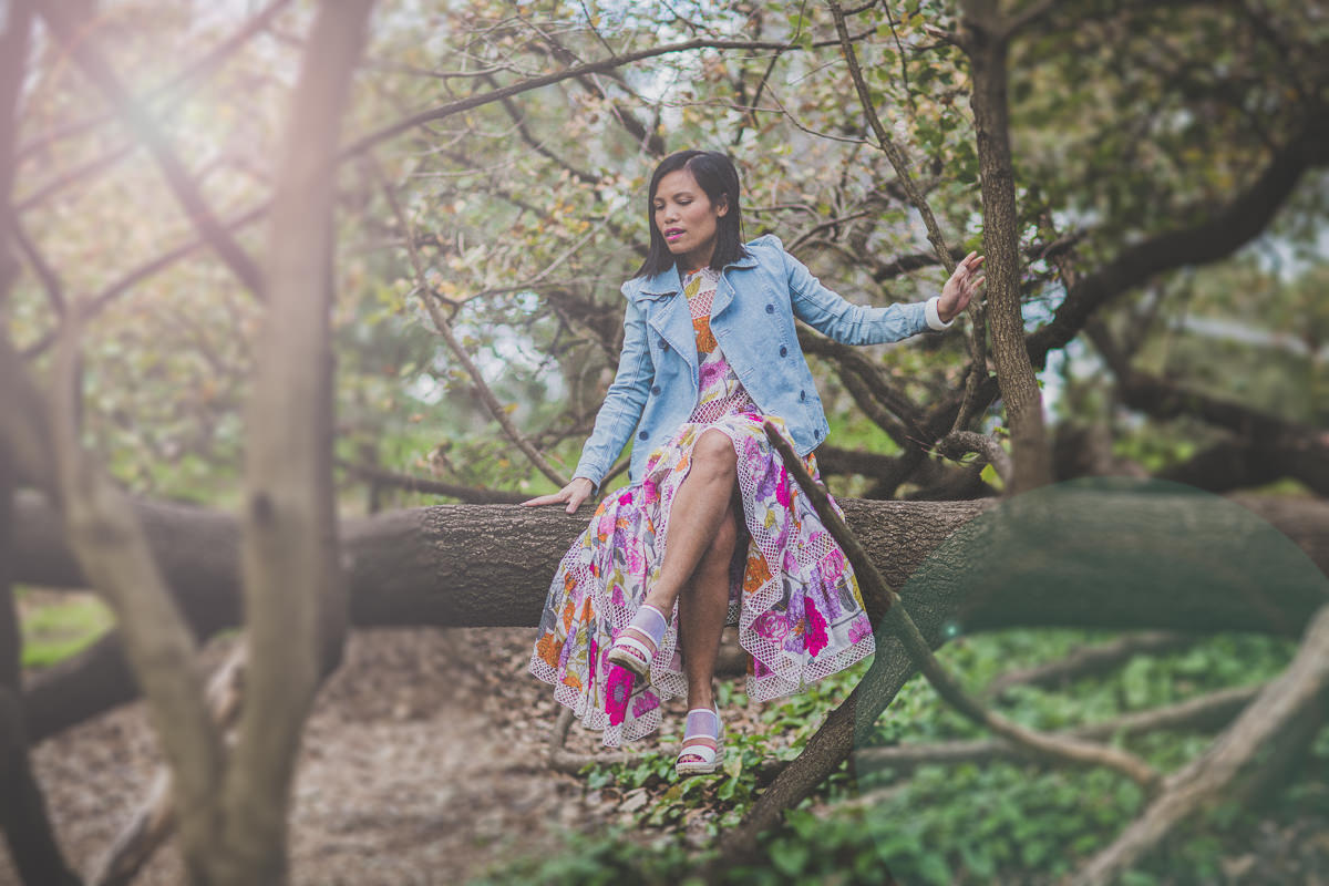 girl sitting on tree in floral skirt