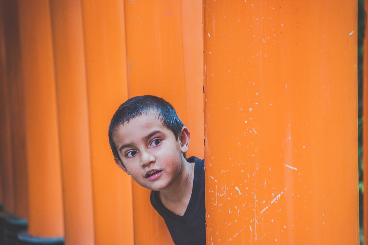 little boy peeking out of the red gates in kyoto - kids photography