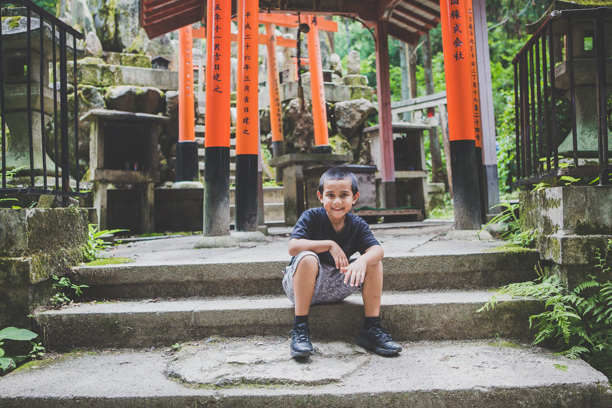 little boy having a break after climbing the temple hill