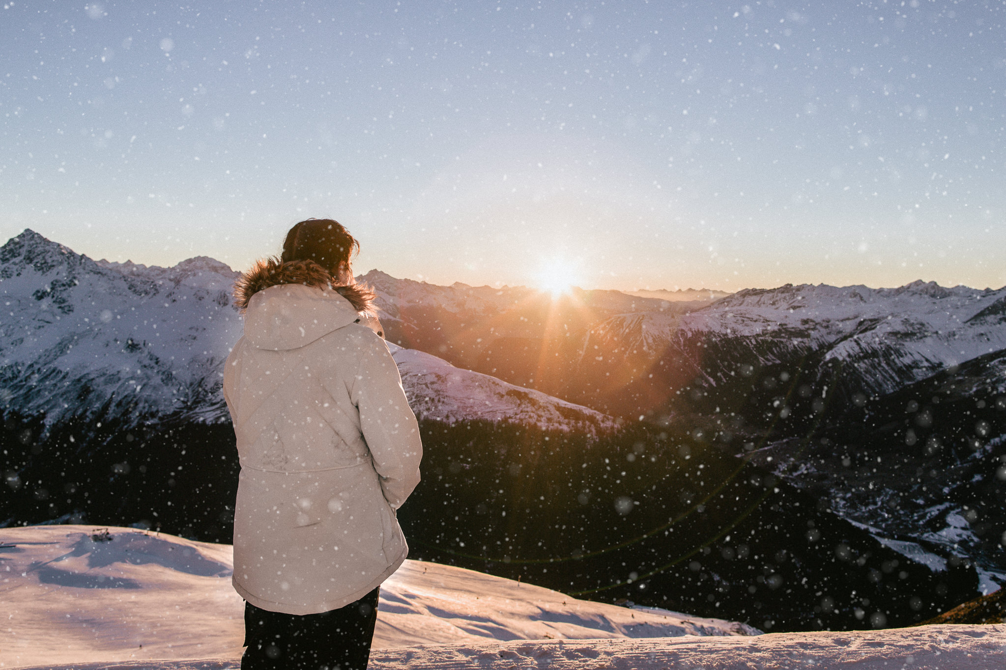 Winter holiday in Europe - Girl looking out in the alps at sunset