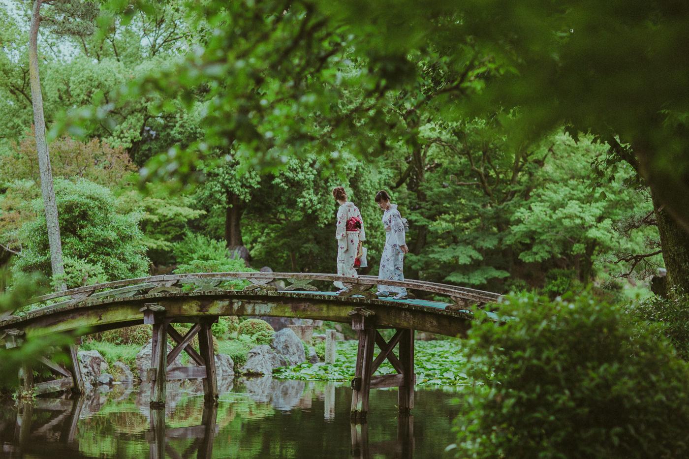 geishas in japanese garden on bridge
