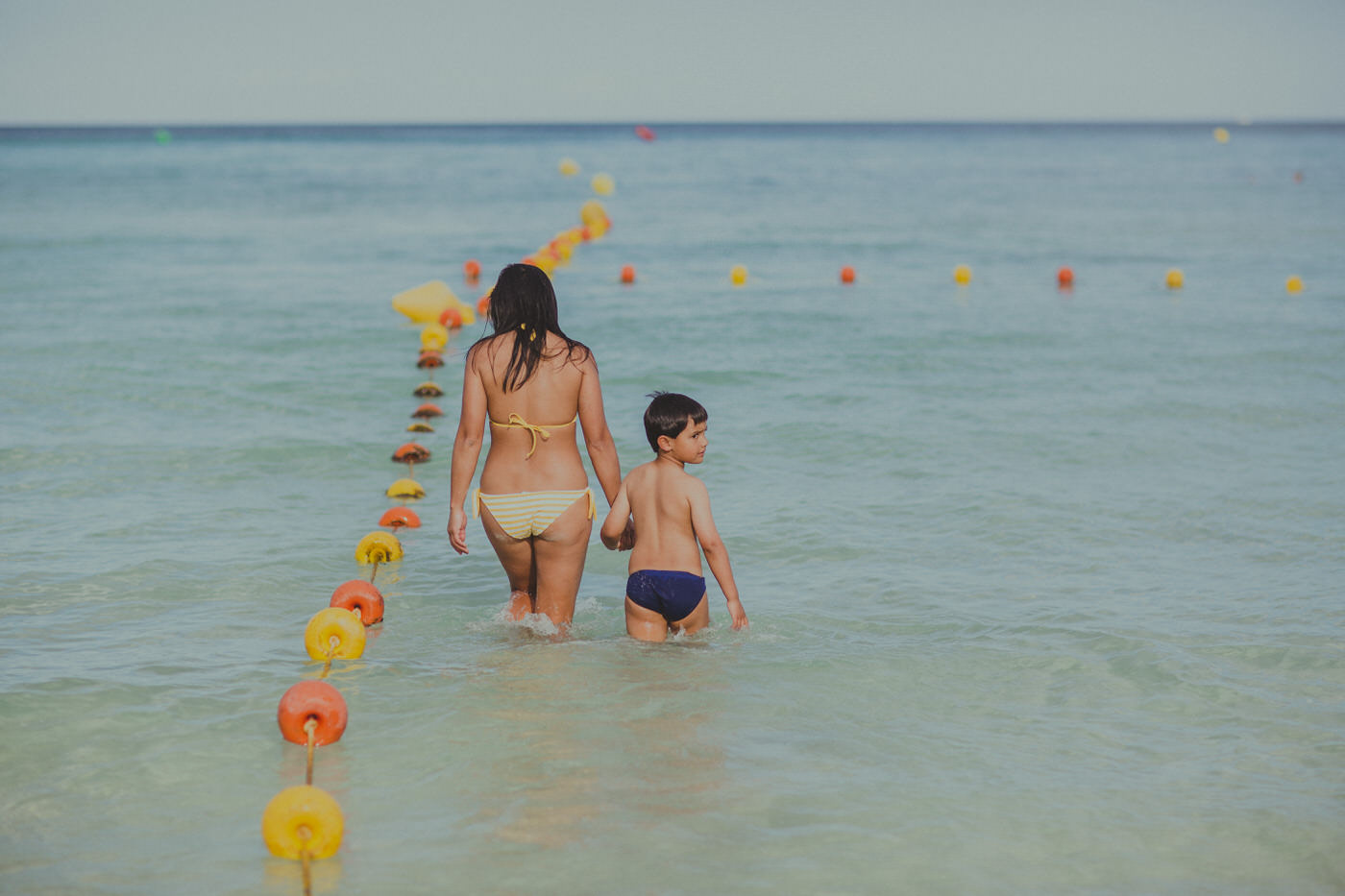 mother and son in the ocean walking along some yellow and orange buoys - happy beach llife