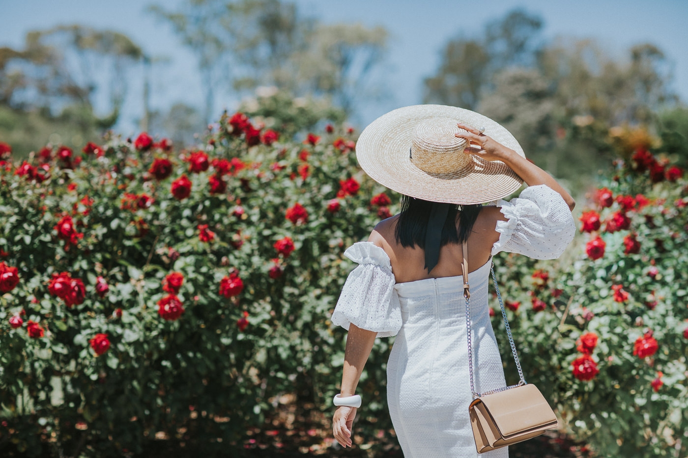 girl from back not showing face with large hat and roses
