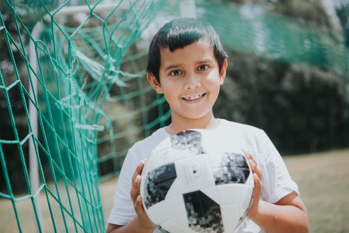 boy holding soccer ball - with net in the background - soccer advertising photo