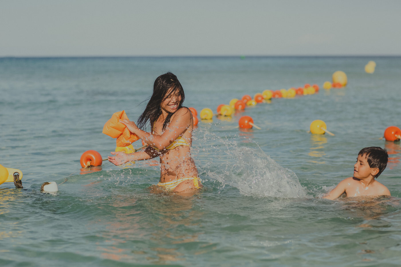 fun in the ocean - girl getting splashed by little boy - swimwear - ocean - fun - happy orange and yellow