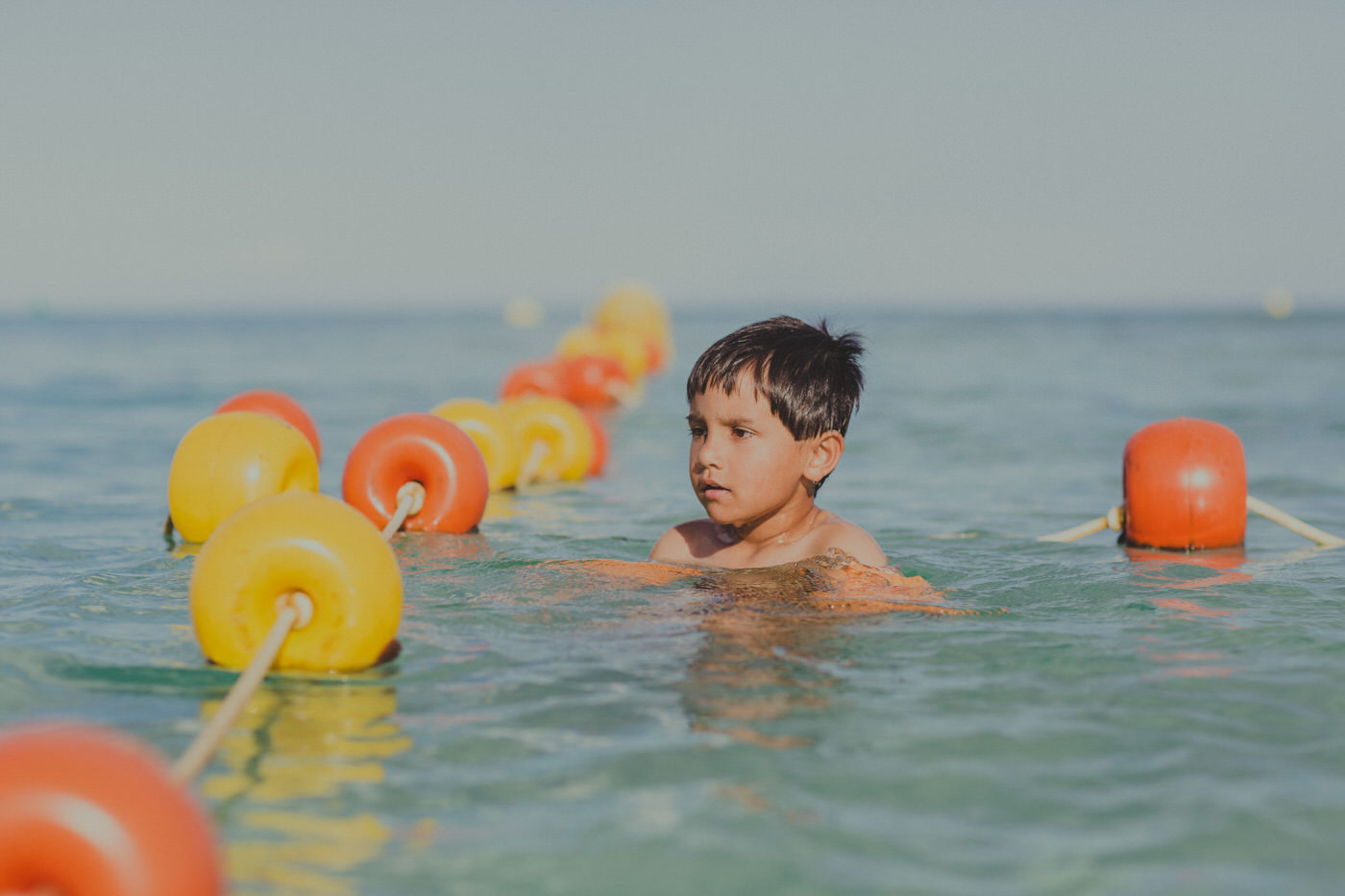 boy swimming in the ocean with colourful (yellow and red) buoys