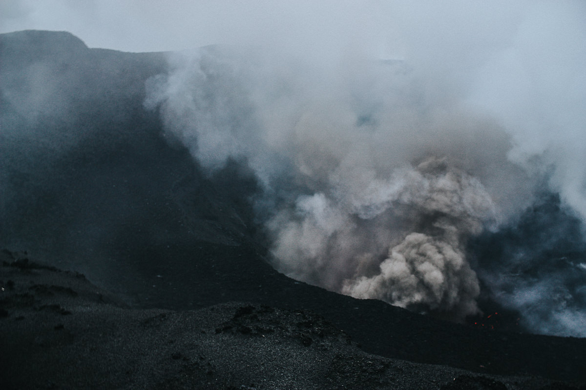 smoke and gas erupting from volcano