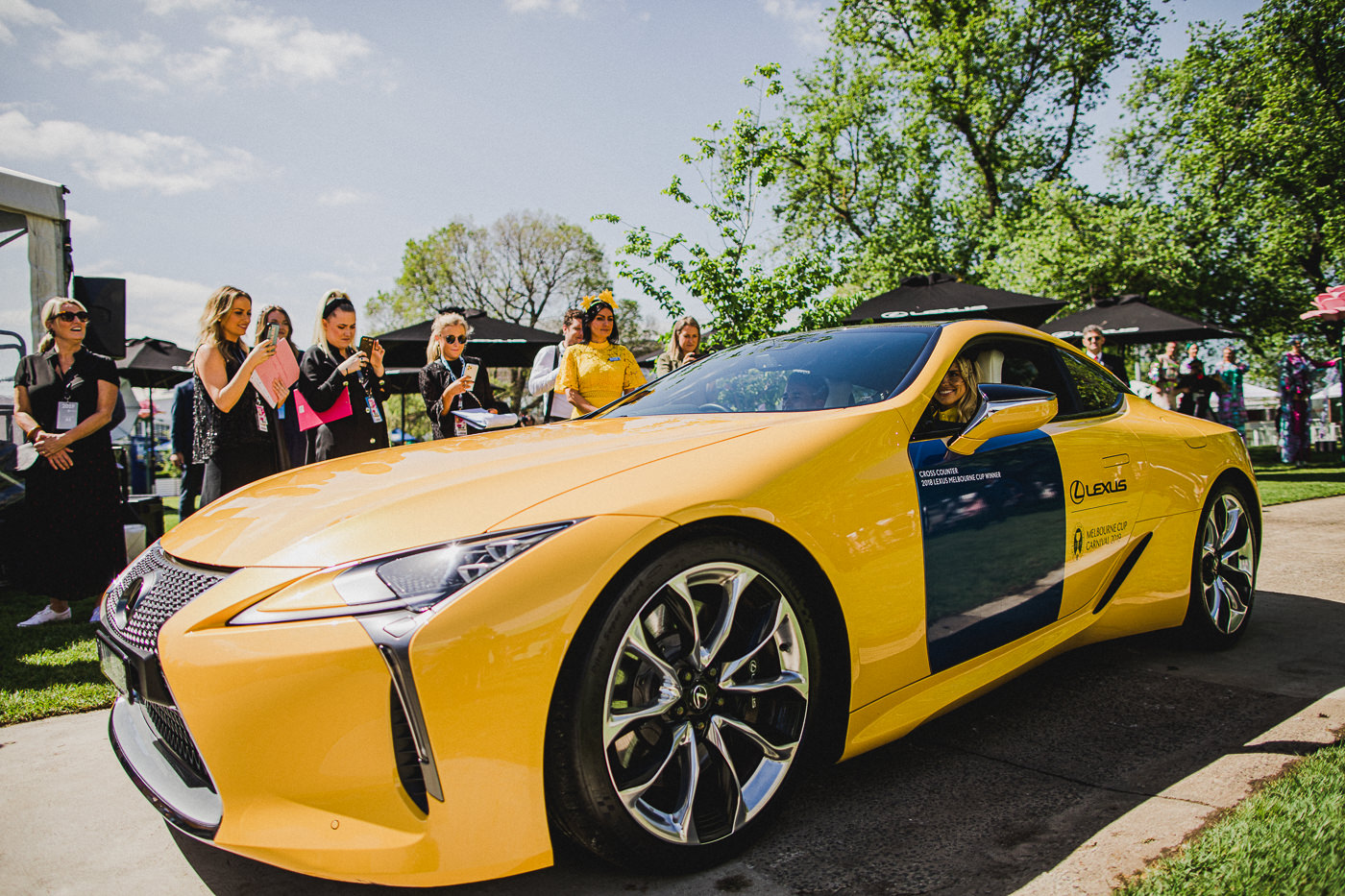 Striking yellow Lexus - LC 500 - Tegan Martin and Lexus ambassador Corey Brown delivered the 2019 Lexus Melbourne Cup trophy to the stage in a striking yellow Lexus LC 500
