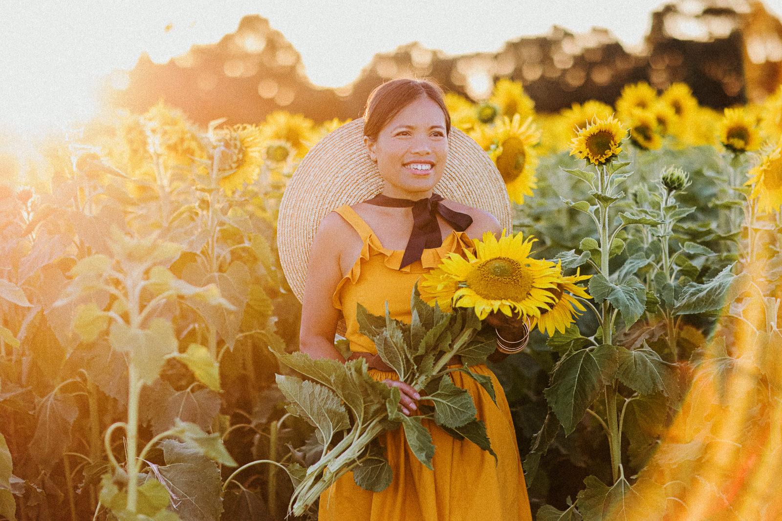 sunset - girl picking sunflowers in field at sunset - creative sunflower photos